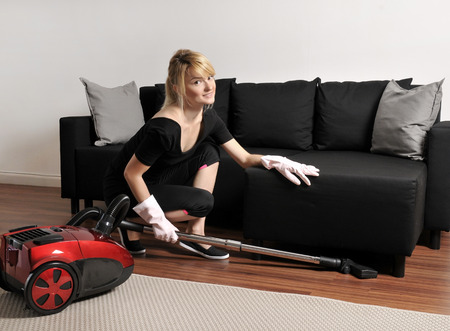 woman on couch: House cleaning, woman vacuuming couch in house Stock Photo
