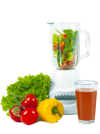 blending: Blender inside with sliced vegetable, fresh tomato and pepper and glass of tomato juice