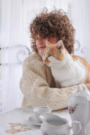 Happy woman in warm sweater with curly hair, smiling and cuddling with red cat Фото со стока