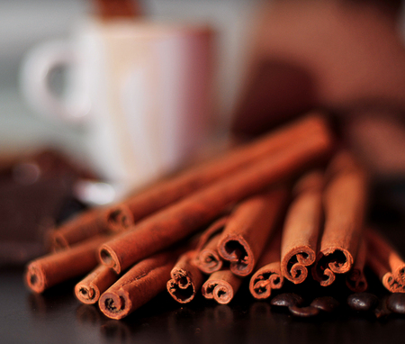 Cup of coffee and cinnamon on wood table