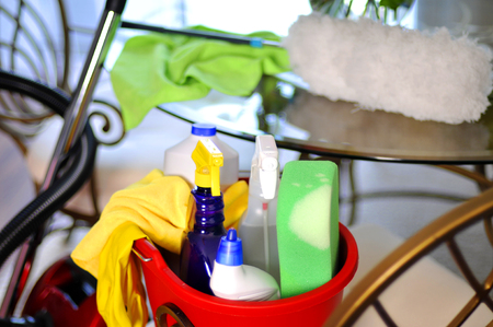 microfiber: Bucket with cleaning supplies and vacuum cleaner near table