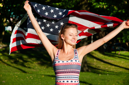 patriot: Young happy patriot girl holding the american, united states flag Stock Photo