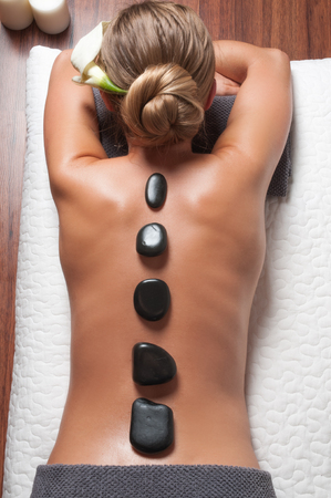 Beauty treatments woman getting spa on a stone therapy, hot stone massage. Girl resting at spa salon on vacation Stock Photo