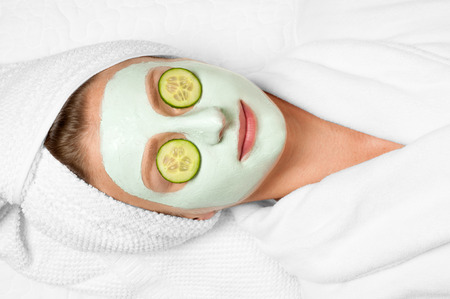 Beautiful young woman is getting facial clay mask at spa, lying with cucumbers on eyes 免版税图像
