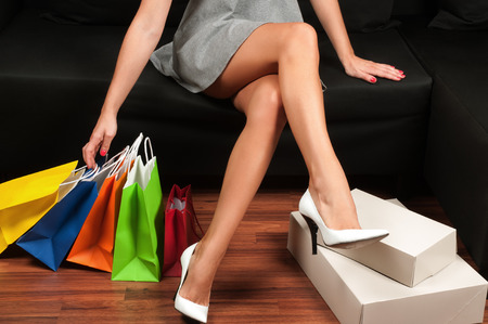 Beautiful female slender legs, Woman holding a shopping bags, sitting on a sofa