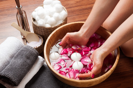 Female hands and bowl of spa water with flowers, hand care in nail salon relaxing manicure with a pink rose flower