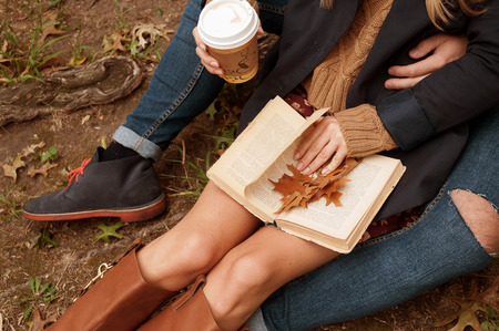 Happy couple in warm knitted hat reading a book outdoor in autumn forest, cozy mood