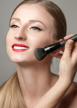 mujer maquillandose: Maquillaje. Mujer de aplicar el maquillaje en su cara. De polvo cosmético del cepillo de maquillaje. Piel perfecta.