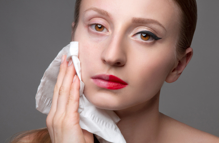 Beautiful woman removing makeup from her face, skin care concept