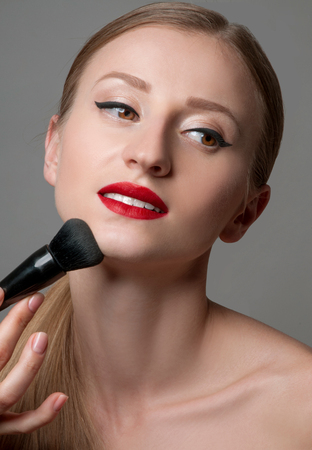 mujer maquillandose: Makeup. Woman Applying Make-up on her Face . Cosmetic Powder Brush for Make up. Perfect Skin.