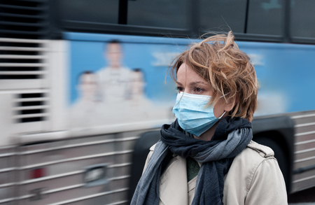 Portrait of woman walking on the street wearing protective mask as protection against infectious diseases.   스톡 콘텐츠