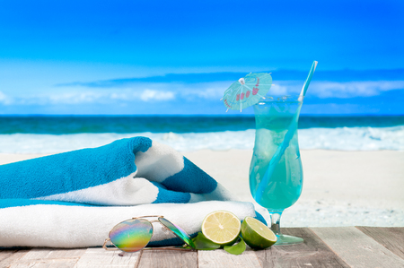 Summer Vacation on the seashore. Glass of fresh cocktail, towel and sunglasses on the beach. Stock Photo
