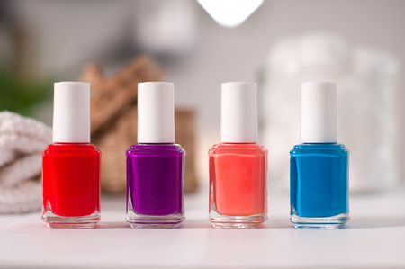Group of bright nail polishes on a table in salon Фото со стока