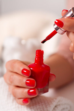 Woman in a nail salon receiving a manicure. Womans hand with red manicure on nails   Stock Photo