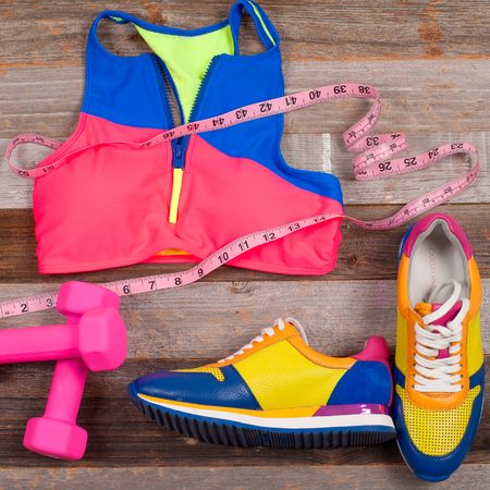 stuff: Gym outfit - workout clothing, sports bra, sneakers, dumbbells, and measure. Female summer swimsuit