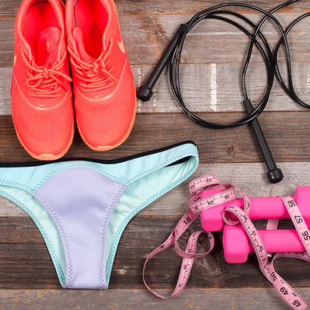 Gym outfit - trainingskleding, zwembroek onderbroeken, sneakers, halters, en maat. Stockfoto