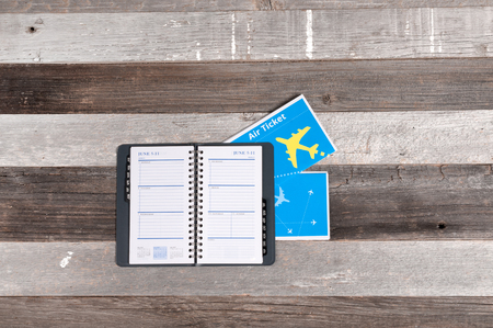Travel concept, flight tickets and notebook on wood table Stock Photo