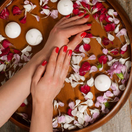 Female hands in bowl of water with flowers, spa salon