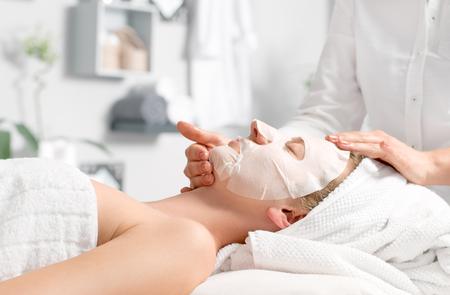 Concepto de tratamiento de belleza. La mujer está recibiendo la máscara facial en el salón del balneario