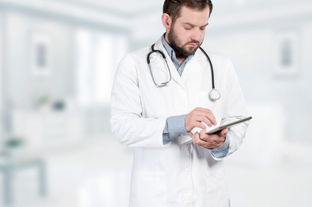 doctoring: Medical doctor with stethoscope around his neck, looking digital tablet