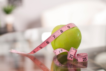 Green apple with measuring tape. Healthy lifestyle concept.