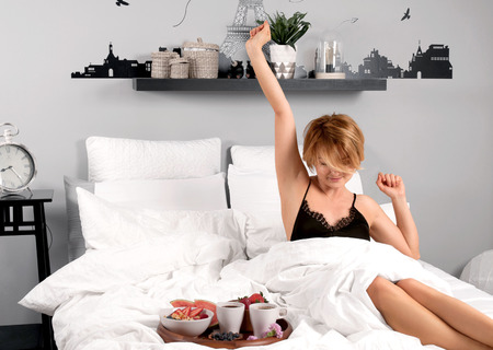 Breakfast. Beautiful woman stretching in bed after wake up. Reklamní fotografie