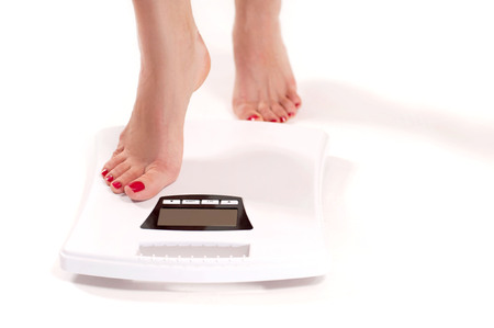 Diet and Weight Loss. Woman standing on weight scale