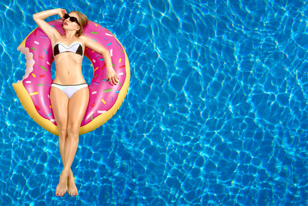 Summer Vacation. Enjoying suntan Woman in bikini on the inflatable mattress in the swimming pool. 스톡 콘텐츠