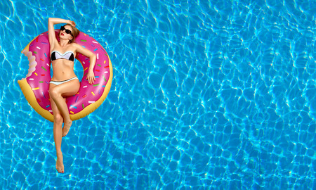 Summer Vacation. Enjoying suntan Woman in bikini on the inflatable mattress in the swimming pool. Archivio Fotografico