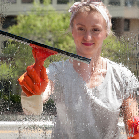Cleaning woman washing windows using a squeegee to wash a window Stock Photo
