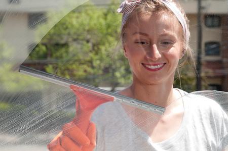 Cleaning woman washing windows using a squeegee to wash a window Zdjęcie Seryjne