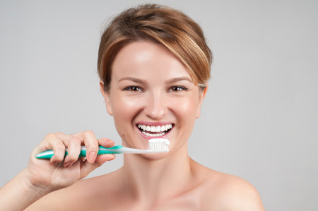 whiten: Happy young woman brushing teeth. Beautiful smile and white teeth