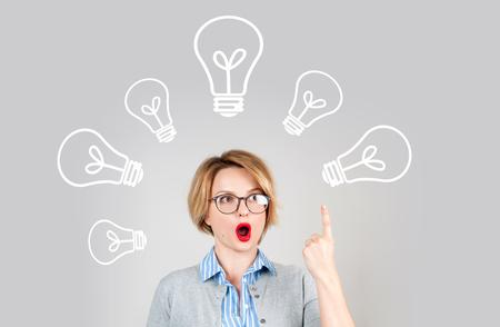 美しいビジネスの女性は、彼女の頭の上の電球指を示す考えを持っています。 ブレーンストーミングしてアイデア コンセプト