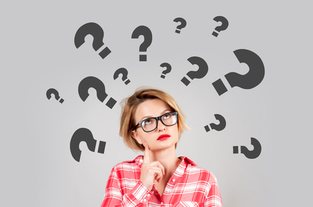 Thinking woman with questioning expression and question marks above her head Stock Photo