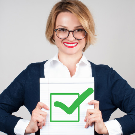 appropriate: Beautiful business woman holding blank paper with check mark or approved icon