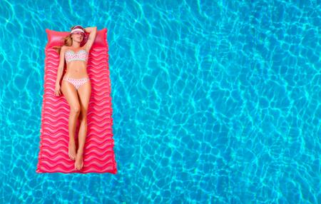 Zomervakantie. Geniet van een zonnige vrouw in bikini op de opblaasbare matras in het zwembad. Stockfoto