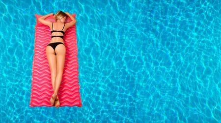 夏休み。スイミング プールで膨脹可能なマットレスの上ビキニで日焼け女を楽しんでいます。