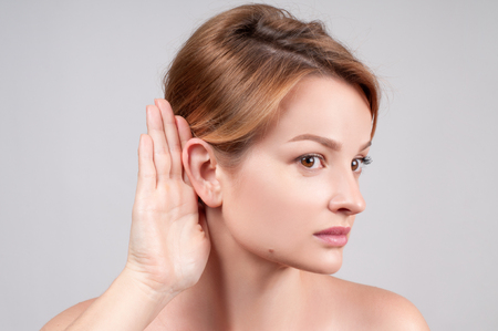Beautiful woman hold hand near her ear and listening carefully