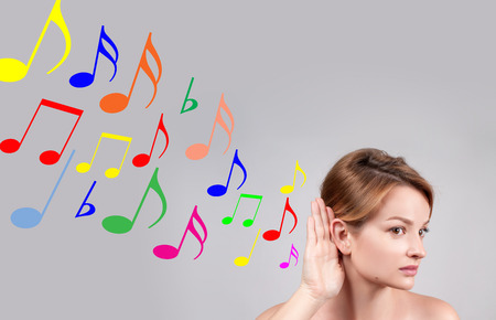 Beautiful woman hold hand near her ear and listening carefully music