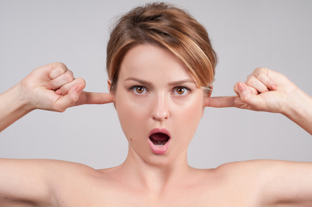 Portrait of woman with open mouth, closing her ears with fingers. Stock Photo