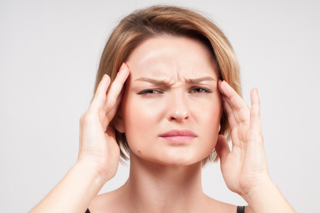 Woman suffers from terrible headaches and compresses the head with fingers