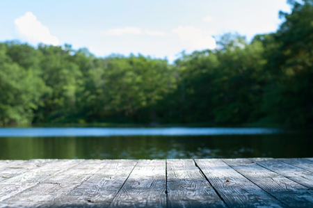 Beautiful forest and lake with a wooden board. Nature background with wooden floor