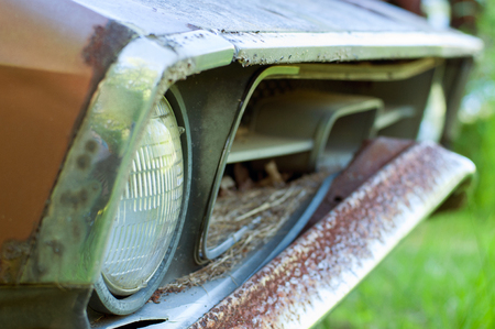 Detail of the front headlight of an old car in abandoned city - vintage style Stock Photo