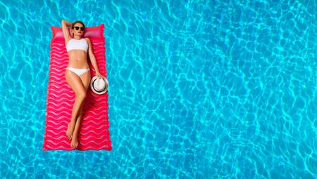 Summer Vacation. Enjoying suntan Woman in bikini on the inflatable mattress in the swimming pool. Banco de Imagens