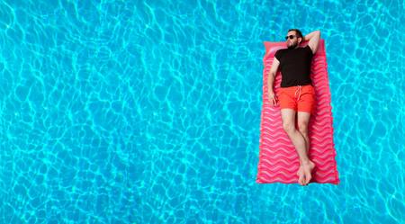 Zomervakantie. Geniet van zonnebrand. Man in t-shirt en shorts op de opblaasbare matras in het zwembad.