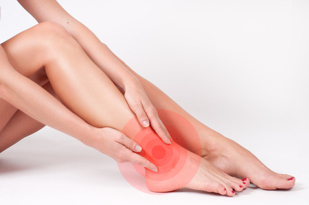 Ankle pain. Woman touching her injured foot. Female legs on white background