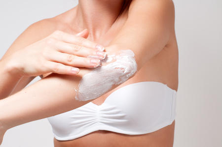 Beauty and Body care. Beautiful woman applying cream on her elbow.