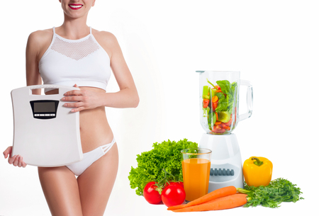 Successful weight loss, slim woman with weight scale. Diet concept, fresh vegetables and fruits