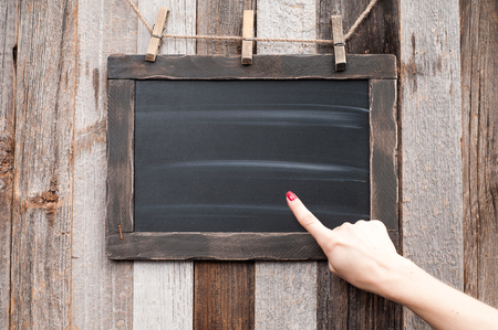 forefinger: Hand showing on Chalkboard. Human hand pointing on blackboard. Stock Photo