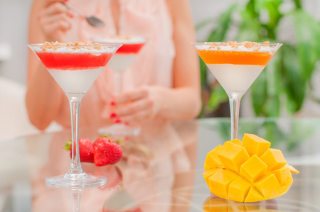 Woman eating dessert. Panna cotta dessert with fruit jelly. Holiday food concept. Stock Photo